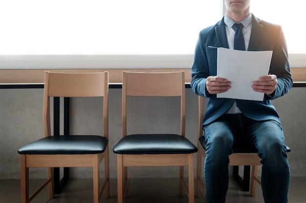 Zelfverzekerde jonge zakenman bedrijf papier terwijl hij op een rij stoelen zit, wachtend op interview.