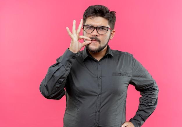 Zelfverzekerde jonge zakenman die een bril draagt die heerlijk gebaar toont dat op roze muur wordt geïsoleerd