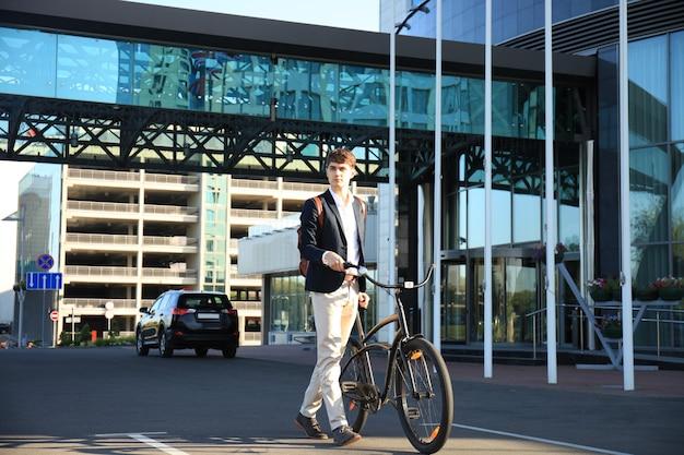 Zelfverzekerde jonge zakenman die met de fiets op straat in de stad loopt.