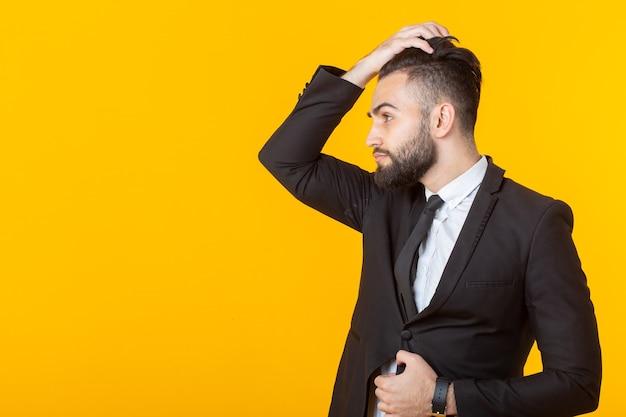 Zelfverzekerde jonge zakenman met een baard maakt zijn haar recht terwijl hij tegen een geel staat