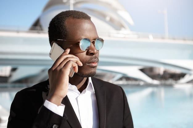 Zelfverzekerde jonge zakenman met zakelijke onderhandelingen over de mobiele telefoon