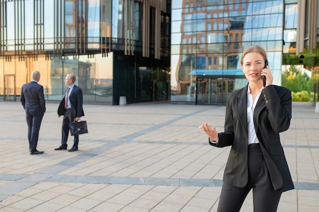 Zelfverzekerde jonge zakenvrouw in kantoor pak praten op mobiele telefoon en buiten gebaren. ondernemers en stad gebouw glazen gevel op achtergrond. kopieer ruimte. zakelijke communicatie concept