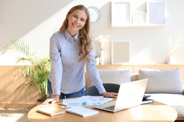 Zelfverzekerde jonge zakenvrouw met een vriendelijke glimlach achter haar bureau in een kantoor aan huis.
