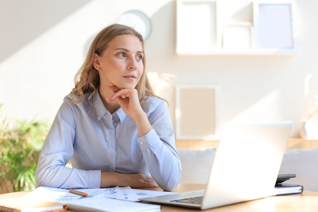 Zelfverzekerde jonge zakenvrouw met een vriendelijke glimlach zit aan haar bureau in een kantoor aan huis.