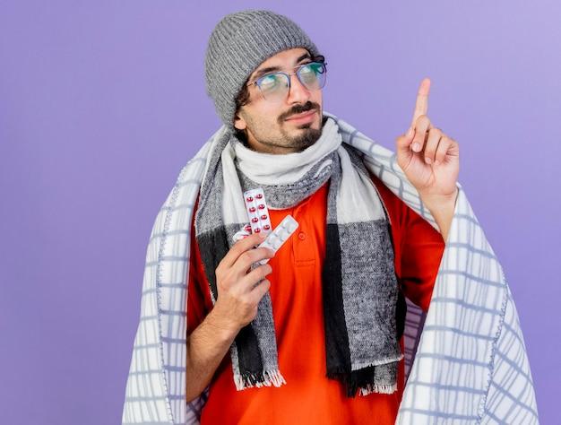 Zelfverzekerde jonge zieke man met bril, muts en sjaal gewikkeld in geruite bedrijf verpakkingen van medische pillen op zoek en omhoog geïsoleerd op paarse muur met kopie ruimte