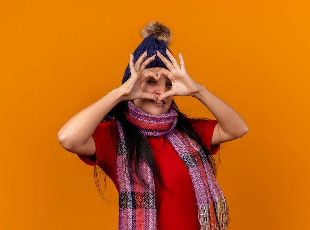 Zelfverzekerde jonge zieke vrouw die de wintermuts en sjaal draagt die hartteken doen die voorzijde erdoorheen kijken geïsoleerd op oranje muur
