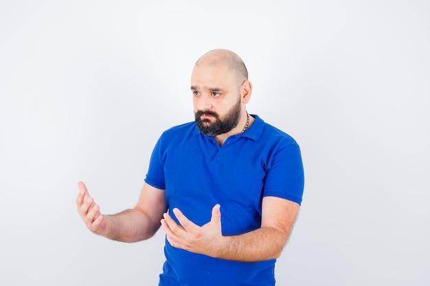 Zelfverzekerde jongeman in blauw t-shirt