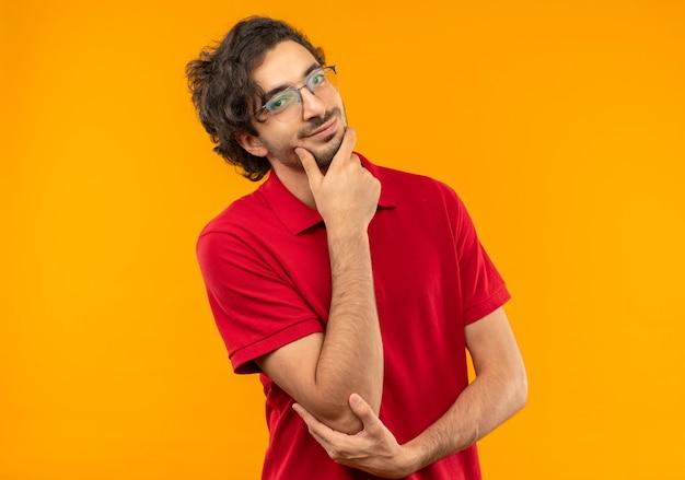 Zelfverzekerde jongeman in rood shirt met optische bril legt hand op kin geïsoleerd op oranje muur