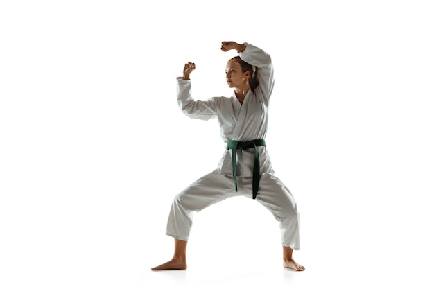 Zelfverzekerde junior in kimono die hand-tot-hand-gevechten beoefent