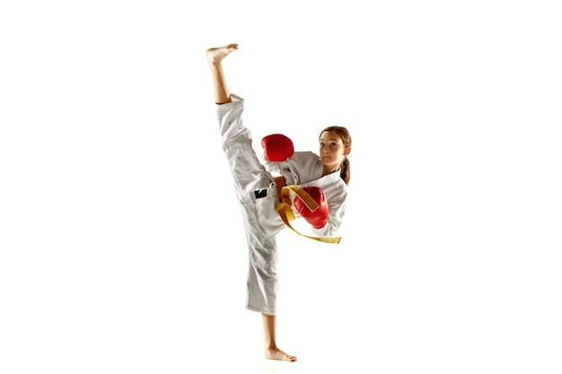 Zelfverzekerde junior in kimono die hand-tot-hand gevechten, vechtsporten beoefent. jonge vrouwelijke vechter met gele riem s opleiding op witte muur. concept van gezonde levensstijl, sport, actie.