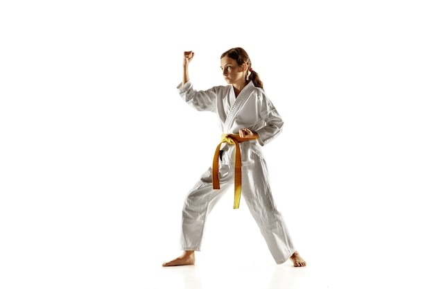 Zelfverzekerde junior in kimono die hand-tot-hand gevechten, vechtsporten beoefent. jonge vrouwelijke vechter met gele riem s opleiding op witte muur. concept van gezonde levensstijl, sport, actie. Gratis Foto