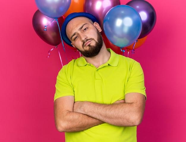 Zelfverzekerde, kantelende jonge man met een blauwe feestmuts die voor ballonnen staat en handen kruist geïsoleerd op roze muur