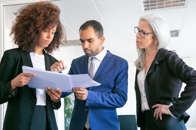 Zelfverzekerde kantoorwerkgevers die documenten samen controleren. drie gefocuste professionele arbeiders die papieren vasthouden en statistische rapporten ondertekenen in de vergaderruimte. teamwork, bedrijfs- en managementconcept