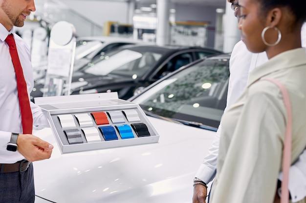 Zelfverzekerde kaukasische professionele adviseur tonen kleurenpalet van auto's aan klanten