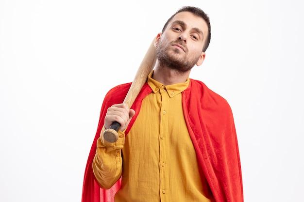 Zelfverzekerde kaukasische superheld man met rode mantel houdt honkbalknuppel op schouder op wit