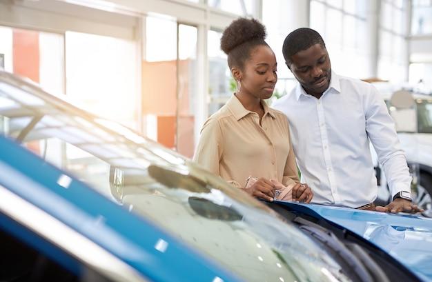 Zelfverzekerde knappe afro man toont zijn vrouw een auto die hij leuk vindt