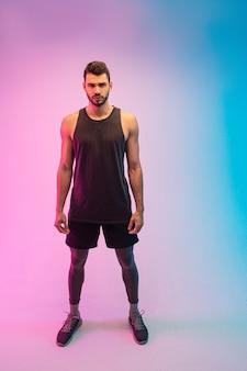 Zelfverzekerde knappe bebaarde europese jonge man. guy draagt tanktop en kijkt naar de camera. geïsoleerd op blauwe en roze achtergrond. studio opname. ruimte kopiëren