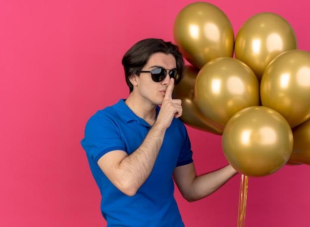 Zelfverzekerde knappe blanke man in zonnebril houdt heliumballonnen vast en gebaren stilteteken