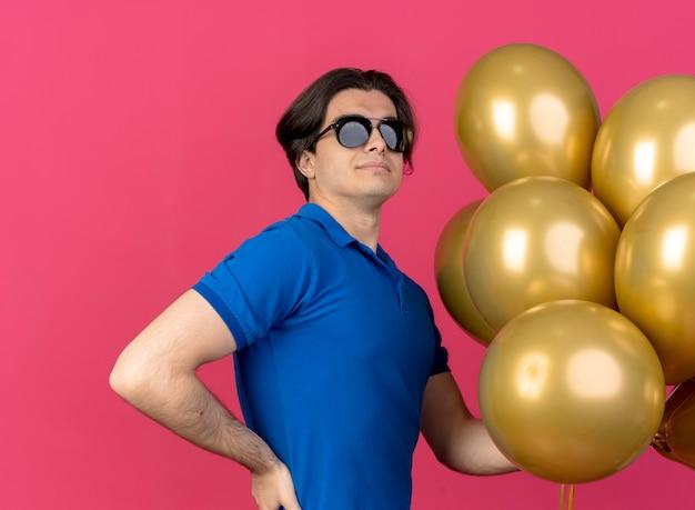 Zelfverzekerde knappe blanke man in zonnebril staat zijwaarts hand op taille en houdt heliumballonnen vast
