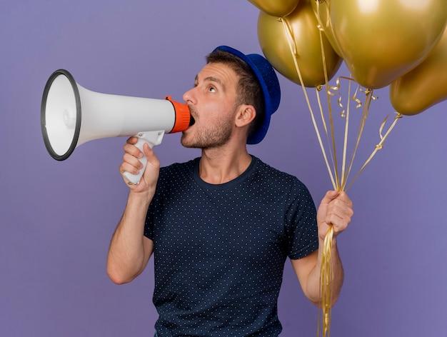 Zelfverzekerde knappe blanke man met blauwe hoed houdt helium ballonnen en spreekt in luidspreker kijken kant geïsoleerd op paarse achtergrond met kopie ruimte