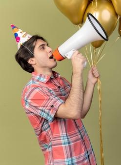 Zelfverzekerde knappe blanke man met verjaardagspet staat zijwaarts met heliumballonnen en spreekt in luidspreker