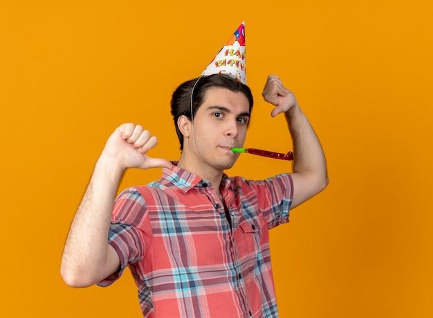Zelfverzekerde knappe blanke man met verjaardagspet wijst naar zichzelf en blaast feestfluitje