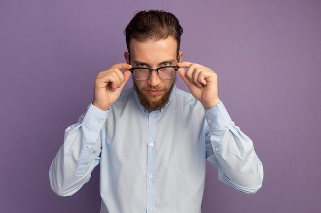 Zelfverzekerde knappe blonde man kijkt door een optische bril geïsoleerd