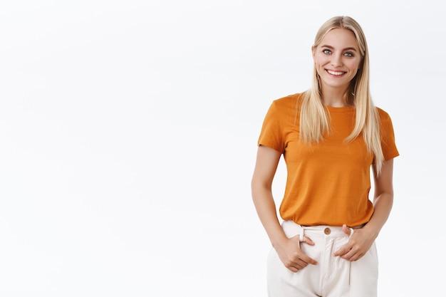 Zelfverzekerde knappe blonde stijlvolle scandinavische vrouw in oranje t-shirt, hand in hand op broek en zelfverzekerd glimlachen, gevoel aangemoedigd startdag met grijns, staande witte achtergrond