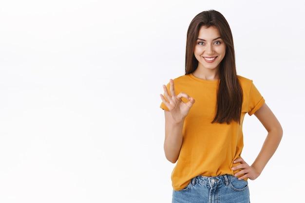 Zelfverzekerde, knappe brutale jonge gelukkige vrouw die oke toont, ok teken in goedkeuring, goed product aanbevelen, glimlachend met wetende, tevreden uitdrukking, staande witte achtergrond verrukt