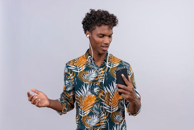 Zelfverzekerde knappe donkere man met krullend haar in bladeren gedrukt shirt in oortelefoons genieten van muziek terwijl hij naar mobiele telefoon kijkt
