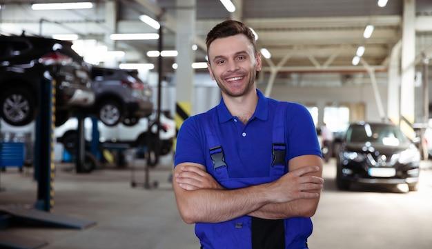 Zelfverzekerde knappe jonge en ervaren autoreparatiewerknemer in werkoverall die zich voordeed tegen de achtergrond van opgeheven auto's in een autoservice