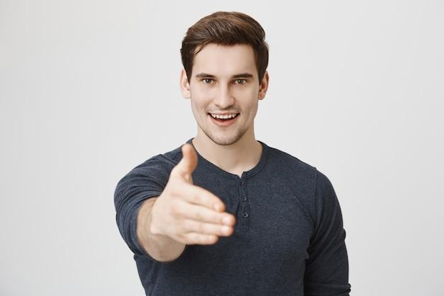 Zelfverzekerde knappe man die zijn hand uitstrekt voor handdruk en glimlachend vastberaden