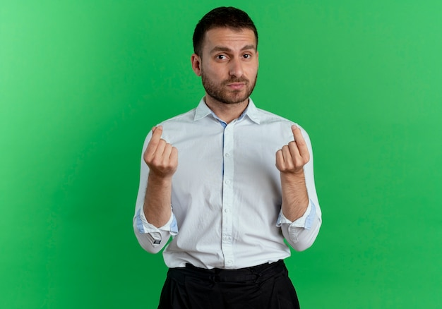 Zelfverzekerde knappe man gebaren geld handteken met twee handen geïsoleerd op groene muur