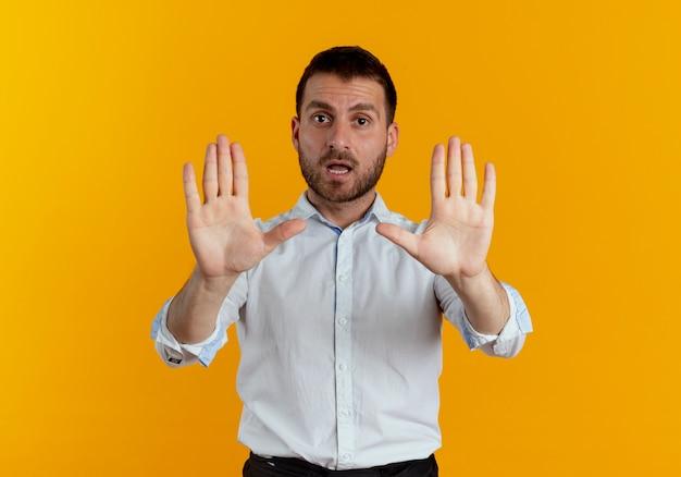 Zelfverzekerde knappe man gebaren stoppen handteken met twee handen geïsoleerd op een oranje muur
