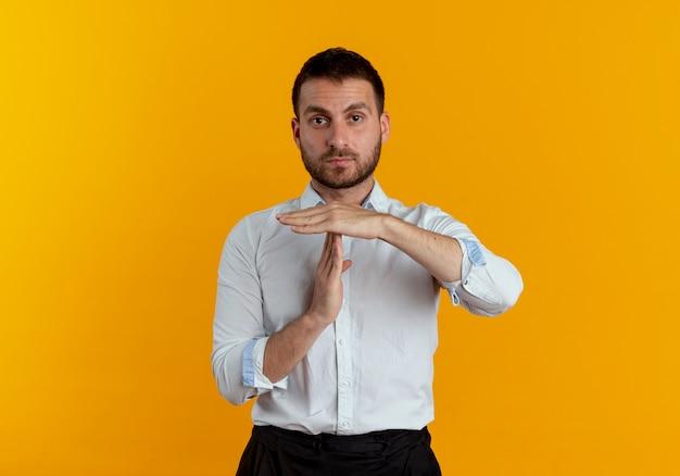 Zelfverzekerde knappe man gebaren time-out handteken geïsoleerd op oranje muur
