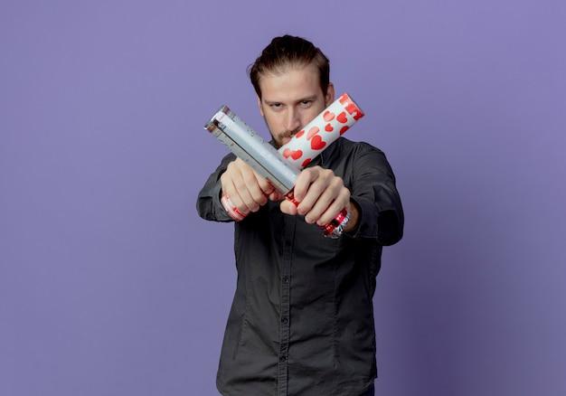 Zelfverzekerde knappe man houdt en kruist confetti kanon op zoek geïsoleerd op paarse muur