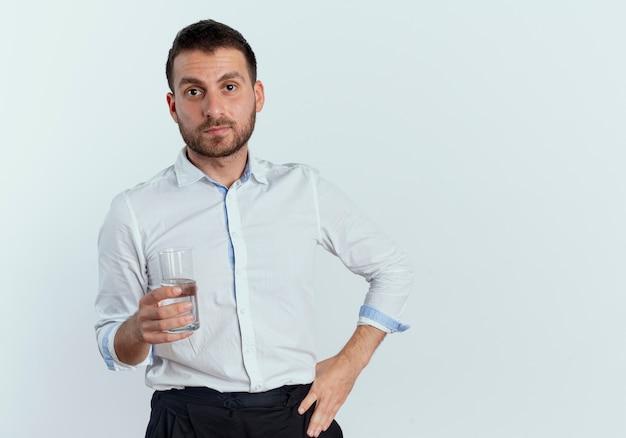 Zelfverzekerde knappe man houdt glas water geïsoleerd op een witte muur
