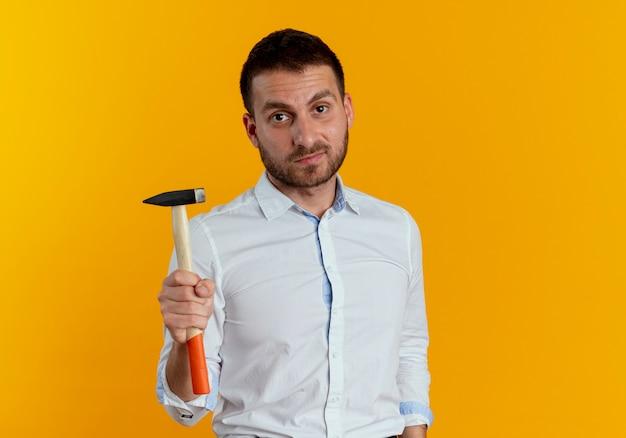 Zelfverzekerde knappe man houdt hamer geïsoleerd op oranje muur