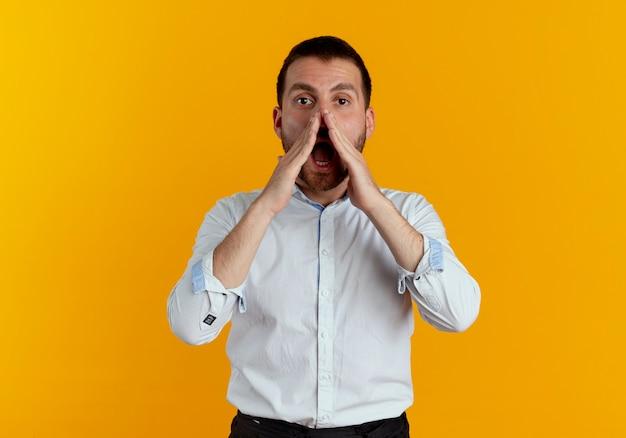 Zelfverzekerde knappe man houdt handen dicht bij de mond en doet alsof hij iemand belt die op een oranje muur is geïsoleerd