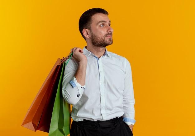 Zelfverzekerde knappe man houdt papieren boodschappentassen op schouder kijken kant geïsoleerd op oranje muur