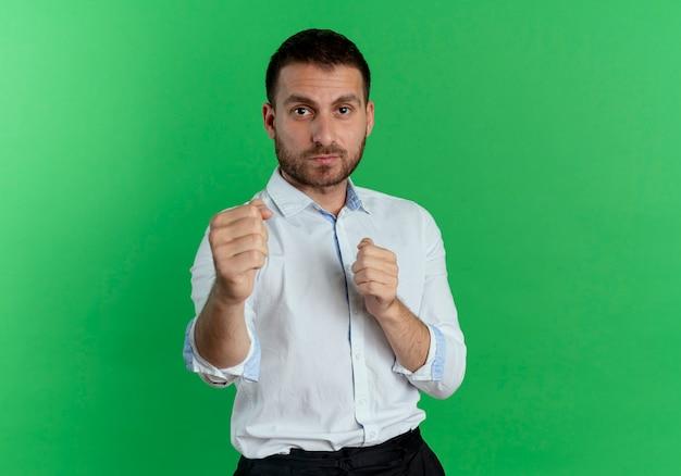Zelfverzekerde knappe man houdt vuisten klaar om te slaan geïsoleerd op groene muur