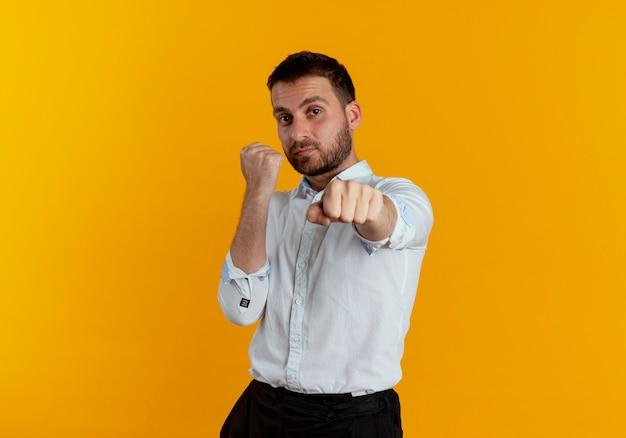 Zelfverzekerde knappe man houdt vuisten klaar om te slaan geïsoleerd op oranje muur