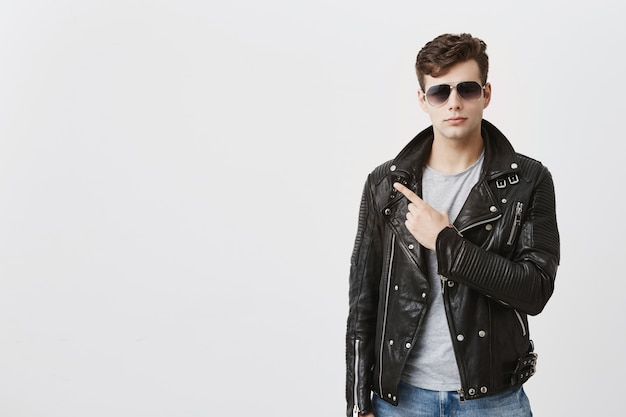 Zelfverzekerde knappe man in zwart lederen jas met zonnebril op, geeft met zijn vinger op kopie ruimte voor reclame of promotietekst. knappe stijlvolle man wijst in de verte