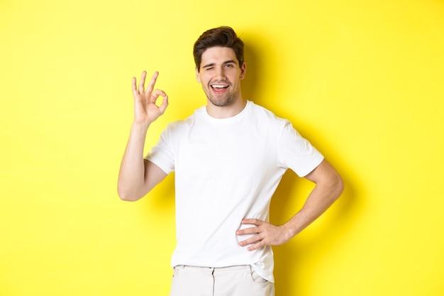 Zelfverzekerde knappe man knipogen, goed teken in goedkeuring tonen, zoals iets goeds, staande op gele achtergrond.