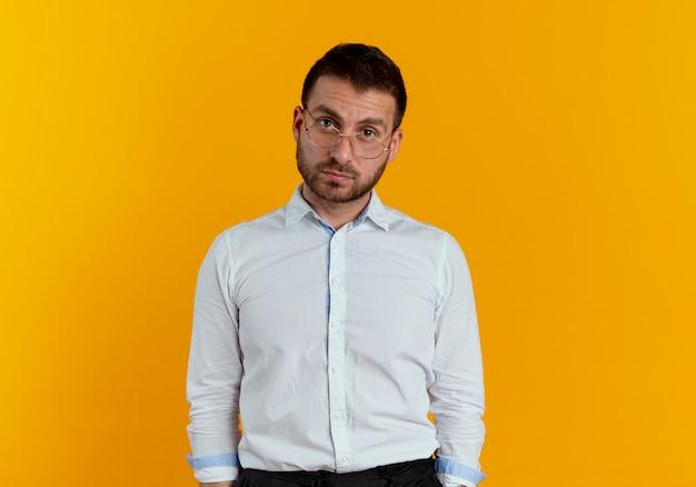 Zelfverzekerde knappe man met optische bril kijkt geïsoleerd op oranje muur