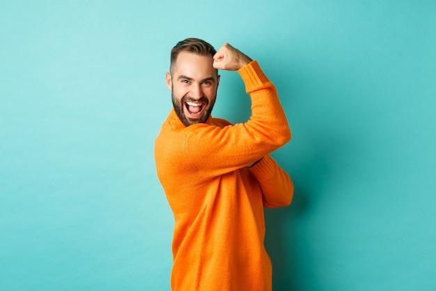 Zelfverzekerde knappe man pronkt met zijn spieren, buigt biceps, voelt zich sterk, staat op een lichtblauwe achtergrond.