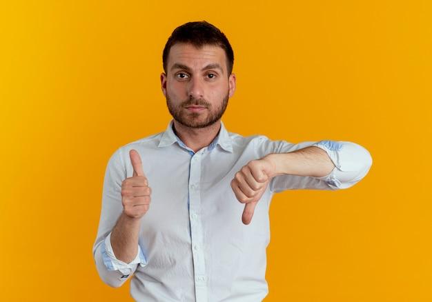 Zelfverzekerde knappe man thumbs up en thumbs down geïsoleerd op oranje muur