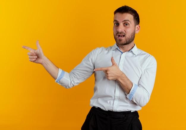 Zelfverzekerde knappe man wijst naar kant met twee handen geïsoleerd op oranje muur