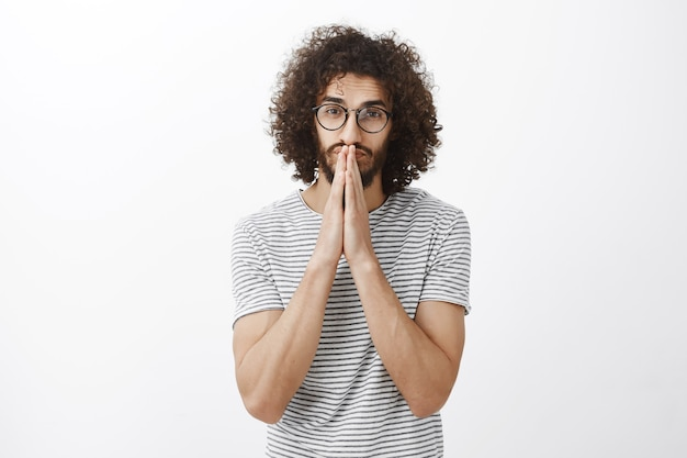Zelfverzekerde knappe spaanse man met krullend haar in trendy zwarte bril, hand in hand bidden over mond en neus