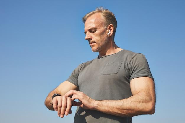 Zelfverzekerde knappe volwassen man in oordopjes permanent tegen blauwe hemel en pols nemen met smartwatch